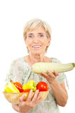 Cheerful aged woman showing zucchini stock photography