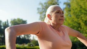 Cheerful aged woman toning her muscles in the upper body. Morning work out. Waist up of a positive aged woman warming up and toning her muscles in the upper body stock video footage