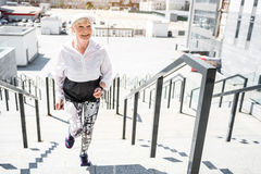 Cheerful aged woman training on steps with guard rails outdoors. Happy old lady is climbing upstairs huge city ladder with metal handrails. She is doing cardio stock photo