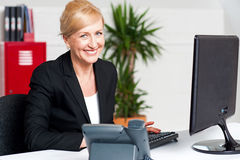 Cheerful aged woman working at the desk royalty free stock image