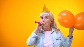 Cheerful aging female with balloons celebrating birthday, positive attitude. Stock photo stock photography
