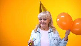Cheerful aging woman with balloons celebrating birthday, positive attitude stock photography