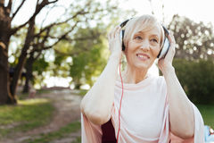 Cheerful aging woman enjoying music in headphones outdoors. Getting happy vibes . Delighted retired charming woman using headphones while enjoying free time royalty free stock photo