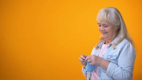 Cheerful aging woman knitting and smiling to camera, family traditions, hobby. Stock footage stock video footage