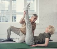 Glad old couple working out at fitness studio. Cheerful aging women lying on carpet with raised legs. Her husband sitting beside her. They are looking at each Royalty Free Stock Photos