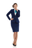 Cheerful Air Stewardess Full Length Isolated. Young businesswoman in blue formalwear and high heels is posing with hand on hip and looking at camera. Front view stock photography