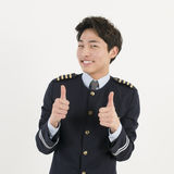 Cheerful airline pilot wearing uniform with thumb up gesture of approval Stock Photo
