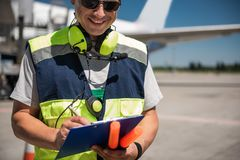 Cheerful airport worker looking at clipboard and writing information. Feeling well. Smiling aviation marshaller noting data while holding signal wands. Runway Royalty Free Stock Photos