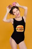 Cheerful amusing woman in swimsut holding donuts over her head royalty free stock photography