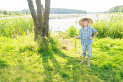 Cheerful angling teenage boy with handmade green twig fishing rod in hand Royalty Free Stock Photography