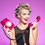 Cheerful angry caucasian woman yelling at retro telephone. stock photography