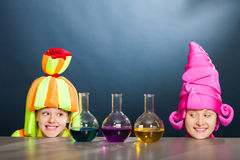 Cheerful animators with chemical flasks and test tubes. Cheerful animators with test tubes jn a dark blue background in studio Royalty Free Stock Image