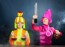 Cheerful animators with chemical flasks and test tubes. Cheerful animators with test tubes jn a dark blue background in studio Stock Images