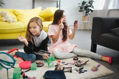 Cheerful ans exited girls sitting on floor in room. They doing makeup. Teenagers look in mirror and use cosmetics. Cheerful ans exited girls sitting on floor in royalty free stock photography