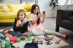 Cheerful ans exited girls sitting on floor in room. They doing makeup. Teenagers look in mirror and use cosmetics. Cheerful ans exited girls sitting on floor in royalty free stock images