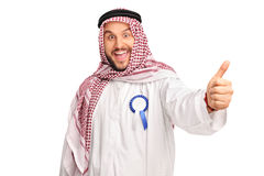 Cheerful Arab with an award ribbon. Young cheerful Arab with a blue award ribbon on his robe giving a thumb up isolated on white background Royalty Free Stock Images