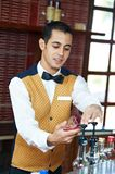 Cheerful arab barman. In uniform preparing cocktail in his hand Royalty Free Stock Images