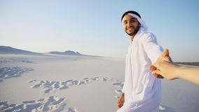 Portrait of beautiful Arabian Sheikh Emirate male tourist guide,. Cheerful Arab male with kindly smile on face leads woman`s arm from camera and shows desert Stock Image