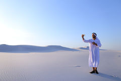 Cheerful Arab male tourist calls friend on Skype by cell and sho Stock Images