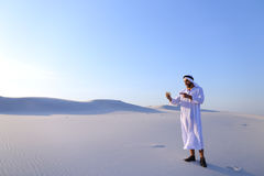 Cheerful Arab male tourist calls friend on Skype by cell and sho Royalty Free Stock Image