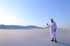 Cheerful Arab male tourist calls friend on Skype by cell and sho Stock Photography