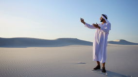 Cheerful Arabian Sheikh male tourist calls friend on videocall by cell and shows surroundings of white sand desert on. Modern handsome Muslim man Arabian Sheikh stock footage