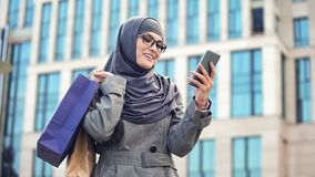 Cheerful Arabic female chatting on phone after shopping, standing outdoors mall. Stock photo royalty free stock photography