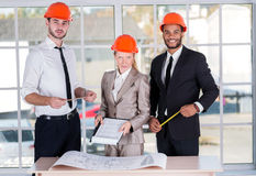 Cheerful architects. Three architects met in the office to discuss business projects. Successful young people in the construction helmets are on the table stock photo