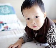 Cheerful asian baby kid lying in bed Stock Image