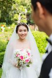 Cheerful Asian bride. Portrait of cheerful Asian bride in wedding dress and veil holding a bouquet Royalty Free Stock Photo