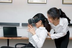 Cheerful Asian business woman having fun with virtual reality glasses in workplace. Cheerful Asian business women having fun with virtual reality glasses in royalty free stock photography