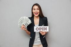 Cheerful asian business woman holding nameplate open and money. While looking at the camera over gray background Royalty Free Stock Image