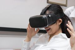 Cheerful Asian business woman wearing virtual reality glasses in office. royalty free stock photos