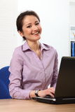 Cheerful Asian business woman working on laptop Stock Photo
