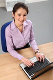 Cheerful Asian business woman working in office Stock Photography