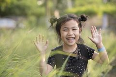 Cheerful asian children kidding playing in green grass field royalty free stock photography