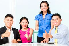 Asian Chinese financial consultants in office. Cheerful Asian Chinese financial consultants in office Royalty Free Stock Photo