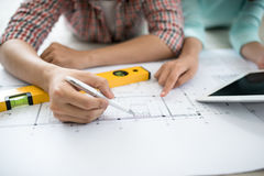 Cheerful asian couple looking at construction house plan stock image