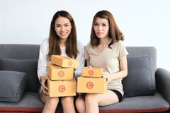 Cheerful Asian entrepreneur owner women with cardboard box sitting on modern sofa at home. Online start up business. Cheerful Asian entrepreneur owner women stock photo