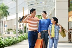 Asian Family with Shopping Bags. Cheerful Asian family of three holding paper bags in hands and sharing emotions with each other after completion of productive royalty free stock photos