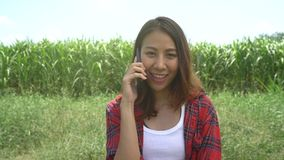Cheerful asian female farmer and entrepreneur posing in the corn crop and smiling using mobile phone. Cheerful asian female farmer and entrepreneur posing in stock video footage