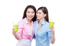 Cheerful asian female friends holding coffee mugs enjoying a conversation Royalty Free Stock Photos