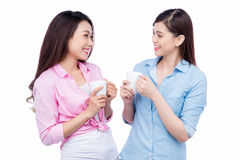 Cheerful asian female friends holding coffee mugs enjoying a conversation Royalty Free Stock Photo