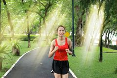 Cheerful Asian fitness runner woman listening music and running exercise in natural park with sunshine effect. Cheerful Asian fitness runner woman listening stock photos