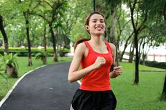 Cheerful Asian fitness runner woman listening music and running in natural park. Cheerful Asian fitness runner woman listening music and running in natural park Stock Photography
