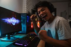 Cheerful asian gamer boy rejoicing victory while playing video g. Ames on computer in dark room wearing headphones and using backlit colorful keyboard stock photo