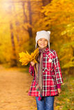 Cheerful Asian girl with bunch of yellow leaves Stock Photography