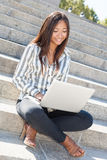 Cheerful asian girl on laptop outdoor Royalty Free Stock Photos