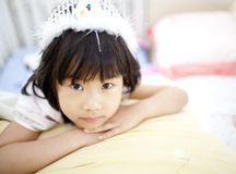 Cheerful asian girl lying in bed Stock Images