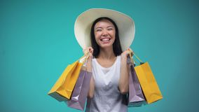 Cheerful asian girl in panama holding many paper bags, shopping, womens hobby. Stock footage stock video footage